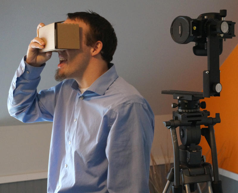 Immersive Technology Studios founder Andrew Glover uses a Google Cardboard virtual reality headset in his Barre office. The studio is Kickstarting the Vermont Peaks project, which will convert vistas from five Vermont mountain tops into VR tours.