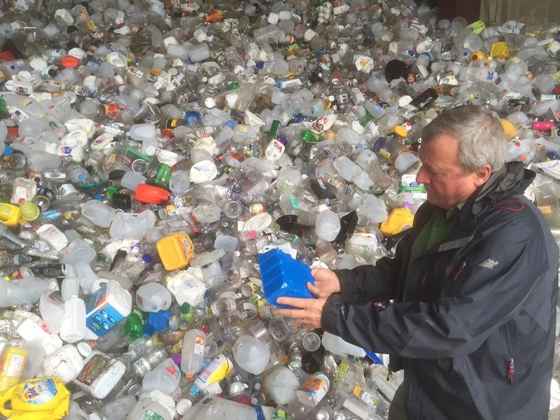 Windham Solid Waste Management District Executive Director Bob Spencer checks out a plastic container at the district facility in Brattleboro. As recycled materials bring in less, districts are trying to figure out how to prepare for new demands.