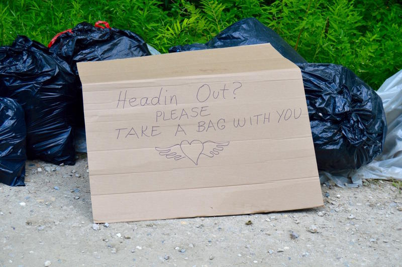 A sign in front of trash during the gathering asks passers-by to take trash out of the forest with them when they leave. Now, as the last few attendees prepare to leave, Forest Service officials are beginning to assess damages to the area.