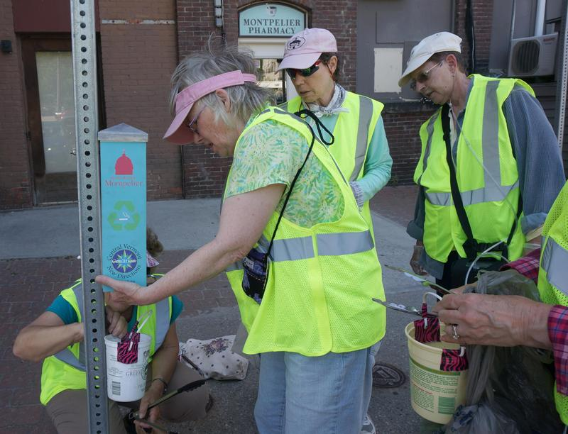 "The Trash Tramps have partnered with other city organizations to install ""Sidewalk Buttlers"" to help keep cigarette butts off the ground and out of the river. Here, Anne Furgeson is unlocking a buttler for its inaugural clean-out."