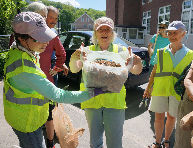 "Anne ""Ben Dover"" Ferguson reveals all the cigarette butts the Trash Tamps collected in one hour while Nancy ""Sister Sludge"" Schulz supports the bottom of the bag. The group meets once a week to pick up litter in Montpelier."