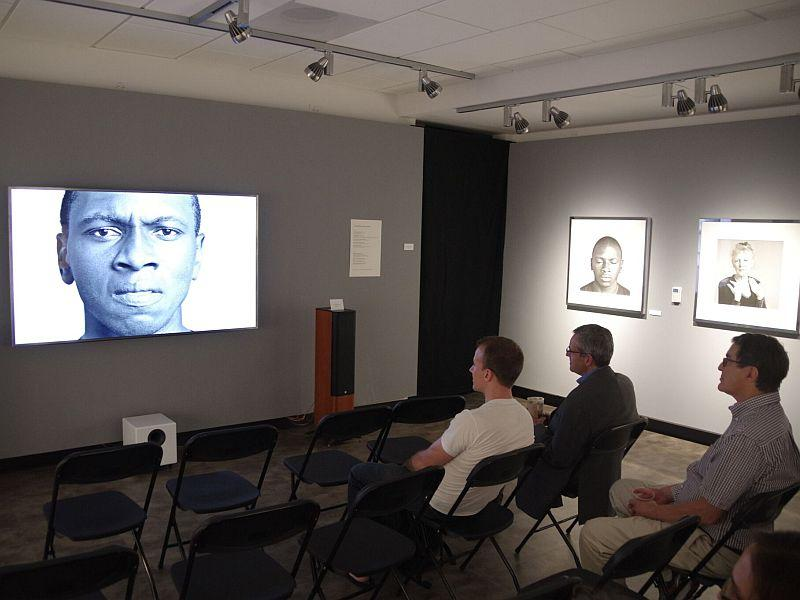 Audience members watch Vermont student and actor Claude Mumbere on a hi-def TV screen while listening to an audio track for Todd Lockwood's latest exhibit, 'Cinema Portraits,' which combines still photography, audio and short film to tell a story.