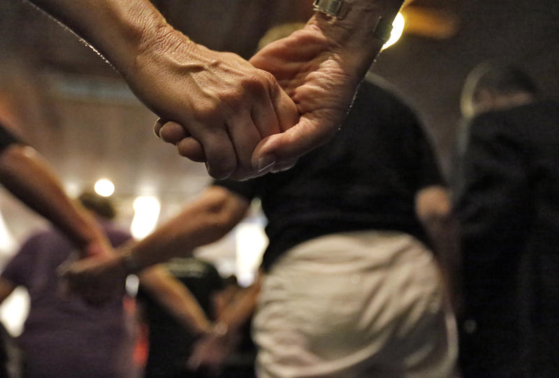 People hold hands during a vigil held at the Joy Metropolitan Church in Orlando, Fla. on Sunday, June 12, in the wake of the shootings at the Pulse Orlando nightclub. Today's show we will focus on Vermonter's reactions to the tragedy.