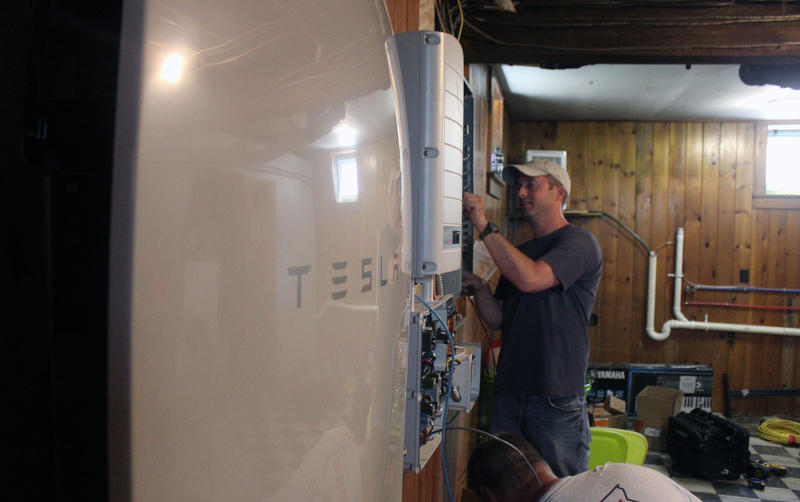 Scott Millette of Peck Electric works on connecting the Tesla Powerwall battery to the electric grid. In-home units like this one are going up around the state as part of a Green Mountain Power pilot project.