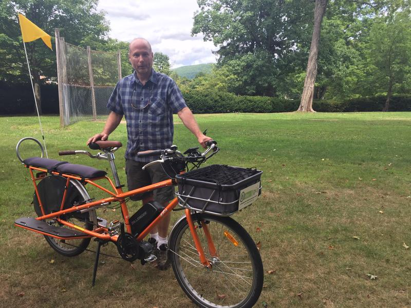 Dave Cohen, founder and director of VBike, stands with a longtail cargobike in Brattleboro. Cohen explains this kind of cargobike has an elongated back with the capacity to hold children or large bags.