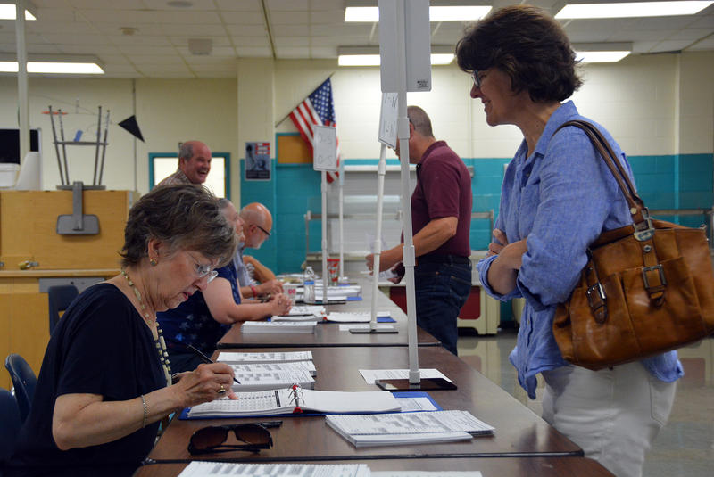 Elaine Helmstutler, left, prepares a ballot for Lisa Dyke at Essex High School on Tuesday afternoon. Follow VPR's coverage of the state primary online and on the air, and bookmark this page to watch the results come in on Tuesday evening.