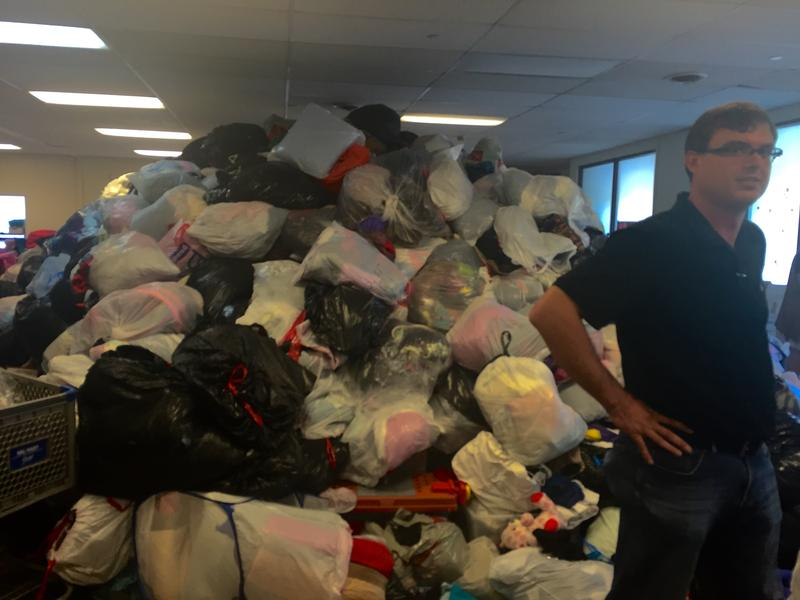 LISTEN's Executive Director, Kyle Fisher, stands in the White River Junction warehouse in front of a pile of donated clothing.