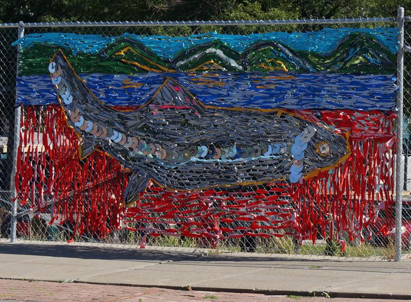 The fish sculpture has been recreated, in fabric and old DVDs, on the Main Street fence.