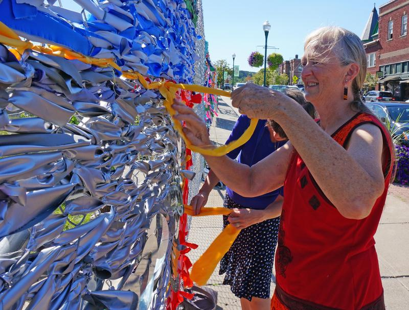 Local artists are dressing up the chain link fence around Newport's stalled Renaissance Block redevelopment project. Here, artist Pam Ladds and Newport City Manager Laura Dolgin work on a mural of a fish, inspired by a sculpture near Lake Memphremagog.