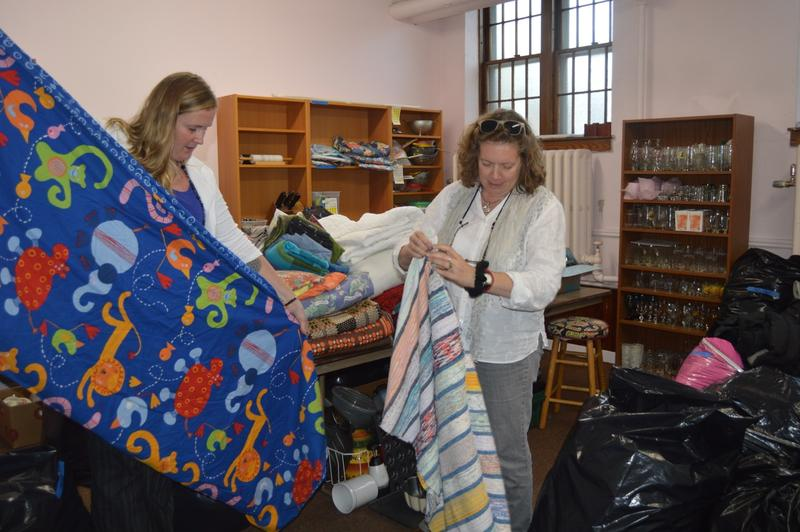 Barb Richter and Marsha Cassel, members of the volunteer group, Rutland Welcomes, fold donated bedding that was collected last month in Rutland.