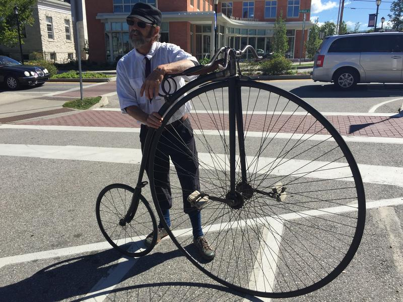 "Glenn Eames, whose bicycle collection is currently on display at the Henry Sheldon Museum, stands in his Wheelmen attire with this 1889 ""Rational Ordinary"" style bike at a demonstration event on Sunday."