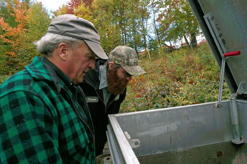 Jefffersonville Village Trustee Tom Wyckoff (front) and water operator Trevor Welch peer down into a spring box, where water is flowing much slower than usual. The village is asking customers to conserve water.