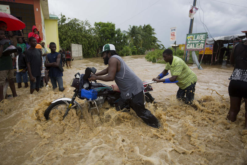 Two men push a motorbike through a flooded street in Leogane, Haiti after Hurricane Matthew hit the country. Pure Water For the World, a Rutland-based nonprofit, has been operating in Haiti since 2007 and is ramping up its efforts to provide clean water.