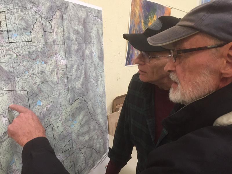Peter Chamberlain, in foreground, and Bill Dunkel, both of WIndham, look over a map of the new layout for a proposed wind development.