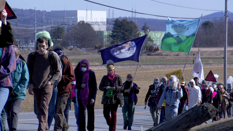 In a still from the new documentary 'Power Struggle,' protesters can be seen marching, with the Vermont Yankee nuclear facility in the background. Filmmaker Robbie Leppzer spoke with VPR about the film.
