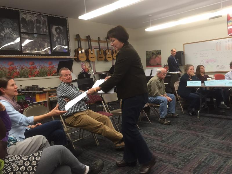 Amy Wall, a member of the Windham Southeast Act 46 committee, hands out the district's Act 46 plan at a recent meeting in Putney.
