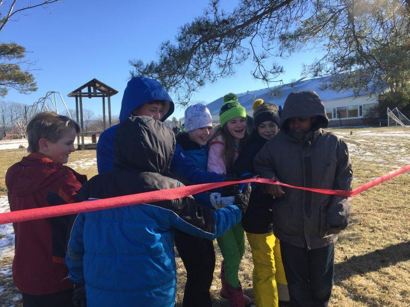 "Members of the sixth-grade class at Bingham Memorial School in Cornwall cut a ceremonial ribbon, officially opening their new ""loose-parts"" playground. It's full of things like stumps and hay, so kids of all ages can build and create together."