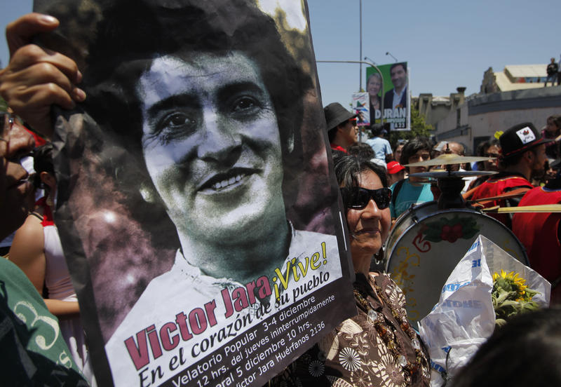 A woman holds a poster of Chilean songwriter Victor Jara, who was killed in 1973, at his funeral procession on Dec. 5, 2009 in Santiago, Chile. Jara is the subject of a new documentary produced by John Summa, which will screen in Burlington on Dec. 8.