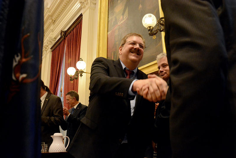 Secretary of State Jim Condos shakes a hand after taking the oath of office for his fourth term.