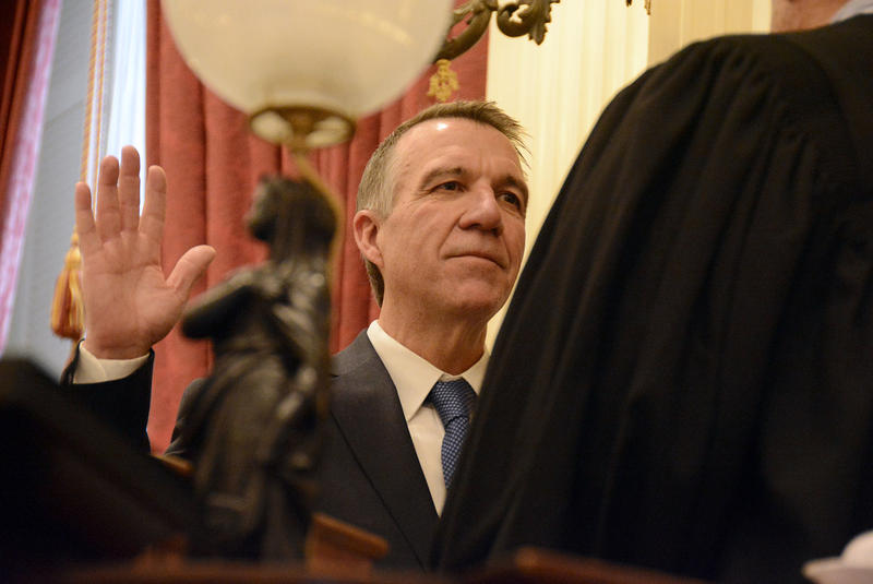 Phil Scott puts his right hand up and is sworn in as Vermont's governor at the Montpelier Statehouse in January 2017.