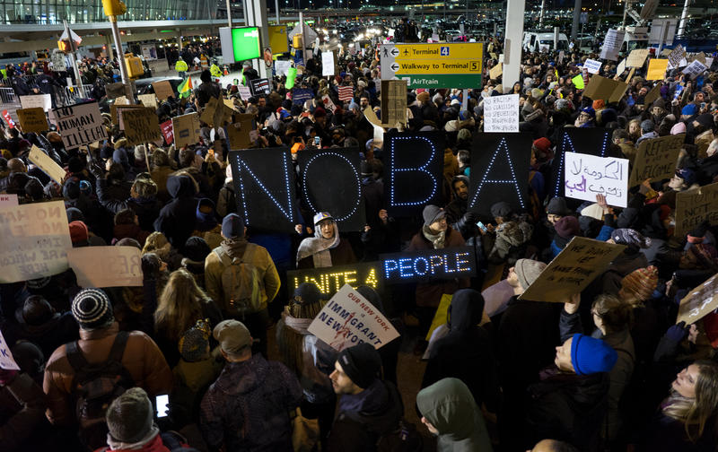 Protesters gathered on Saturday at New York's John F. Kennedy International Airport following news from earlier in the day that two Iraqi refugees had been detained trying to enter the United States.