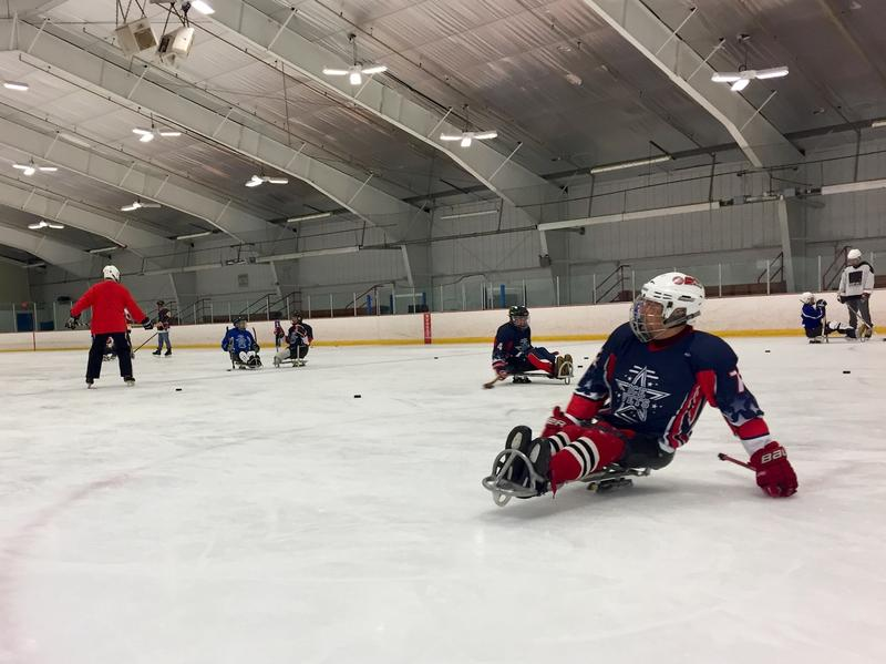 A disabled veteran skates across the James W. Campion III Rink in West Lebanon, N.H. as part of the annual New England Winter Sports Clinic for Disabled Vets. Instead of balancing on two blades, players sit in sleds and balance on one.