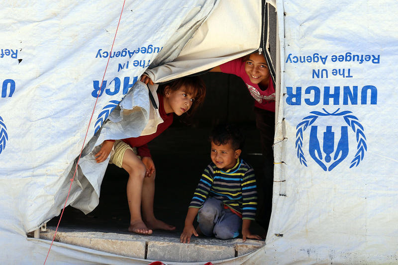Syrian refugee children look from their tent at the Zaatari Refugee Camp, near Mafraq, Jordan, in September 2015.
