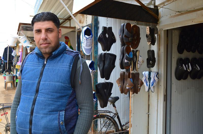 Ayman Alshouly sells shoes at a small shop in the camp. A farmer in Syria, he fled the violence four years ago and met his wife in Zaatari camp.