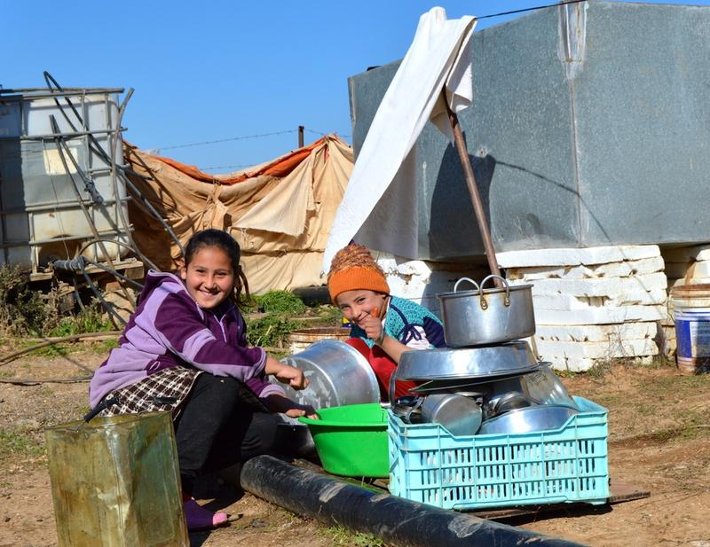 Two of Mariam Mohammed's children wash dishes outside the tents. Because they're far away from the city and refugee camps, the children are not able to go to school.