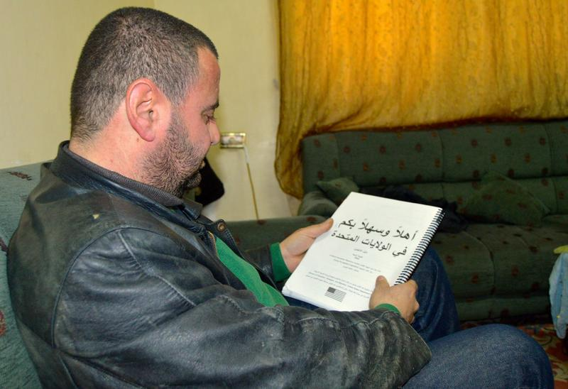 Mohammed Alzoubani, a Syrian refugee living in Amman, Jordan, sits with his American culture and laws workbook. He had been studying in preparation for resettling with his family in Detroit, Mich., but now is not sure what's next for them.