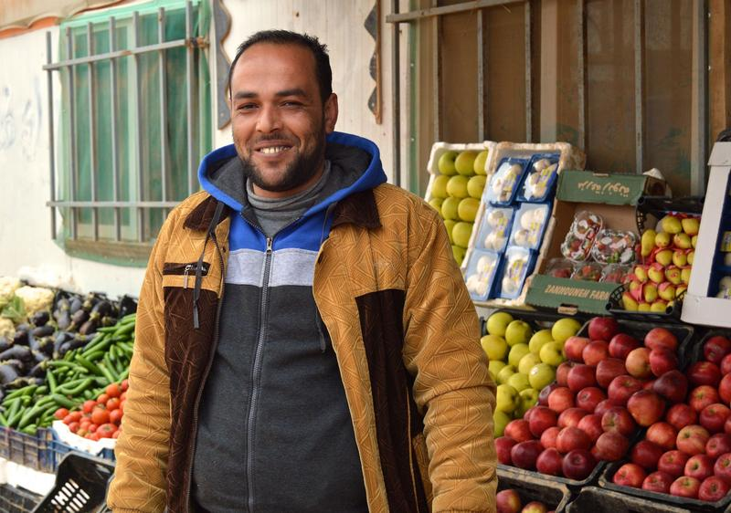 Mohammed Kenawy, who has lived in Zaatari for four years, stands in front of his bustling vegetable and fruit stand.