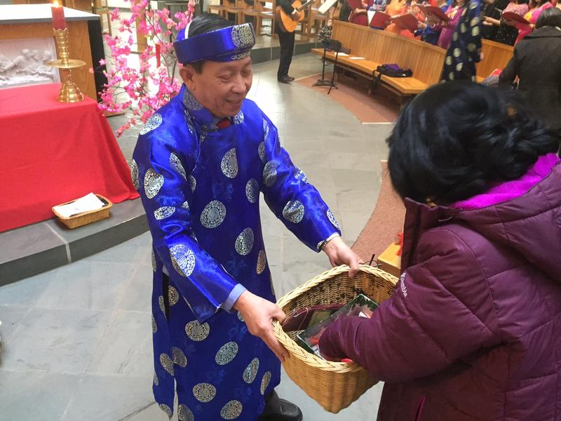 Doan Vu hands out New Year's gifts after Mass at the Cathedral of the Immaculate Conception in Burlington. Once a month, a Vietnamese priest comes down from Montreal to perform Mass in Vietnamese for the local community.
