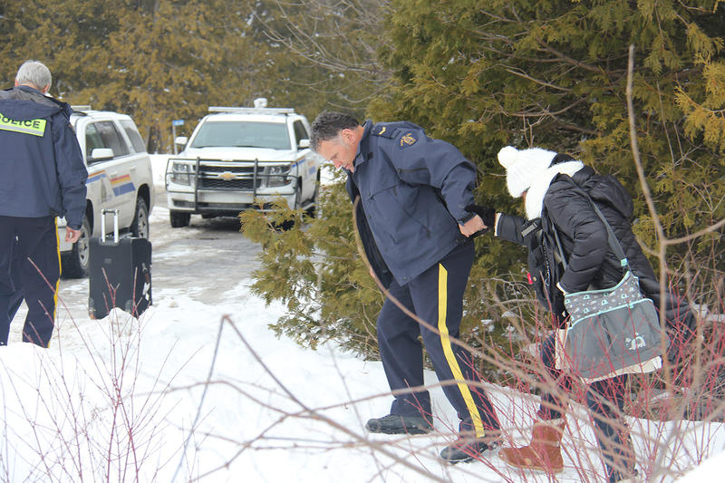 A Canadian police officer offers a hand to a migrant crossing the U.S.-Canada border near Champlain, New York on Wednesday. The Royal Canadian Mounted Police are reporting surges in illegal crossings in Canada in recent months.