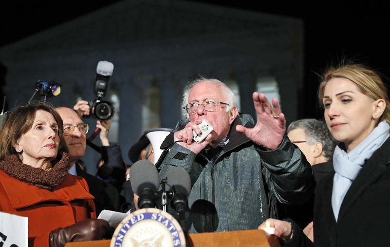 Sen. Bernie Sanders speaks with House Minority Leader Nancy Pelosi of Calif., left, and other members of Congress, in front of the Supreme Court about President Donald Trump's recent executive orders on Jan. 30.