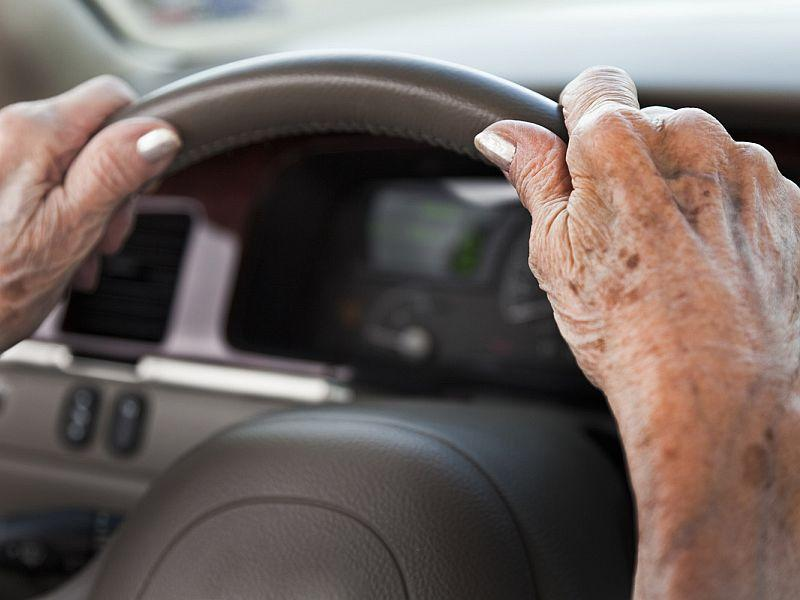Person's hands grabbing a car steering wheel.