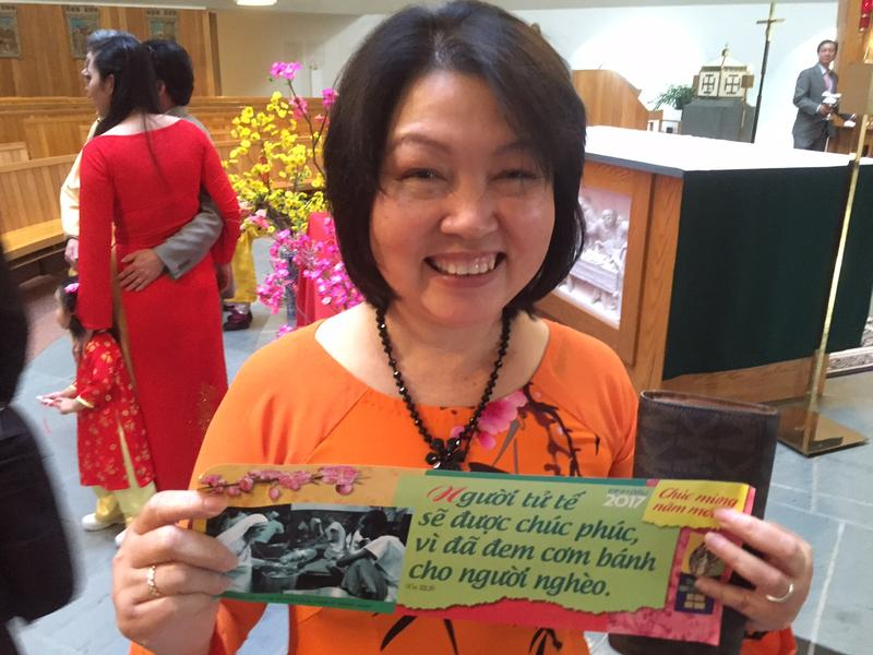 "Vinh Vu holds a special New Year's gift that she picked after a Vietnamese Mass. The paper reads, ""Compassionate people will be blessed for their help of the poor."""