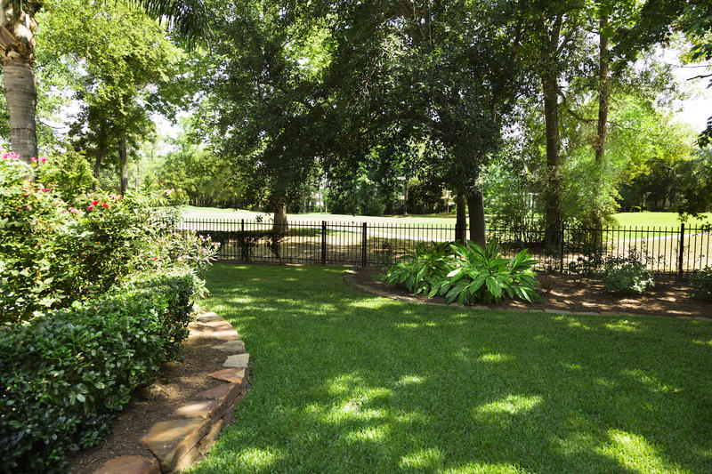 Backyard overlooking golf course, flowerbeds and shrubs.