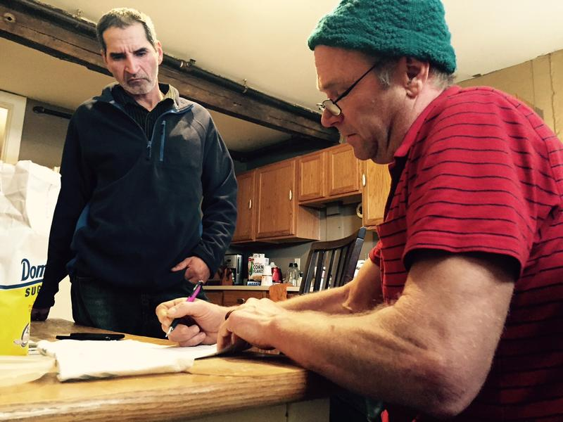 Doug Avery, right, helps Miguel Moreno Gomez fill out a form in English at a farmhouse in southern Vermont.