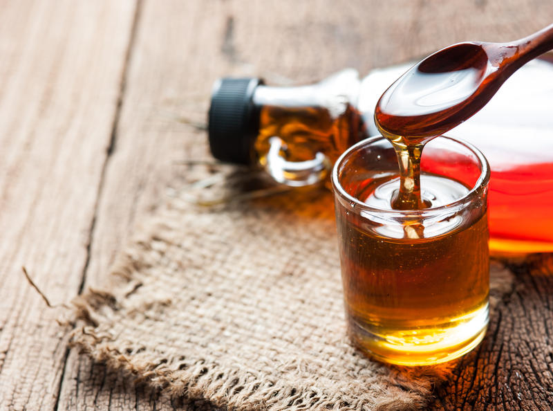 Glass bottle of maple syrup laying down; nearby a spoon drizzles maple syrup into a small glass filled with syrup.