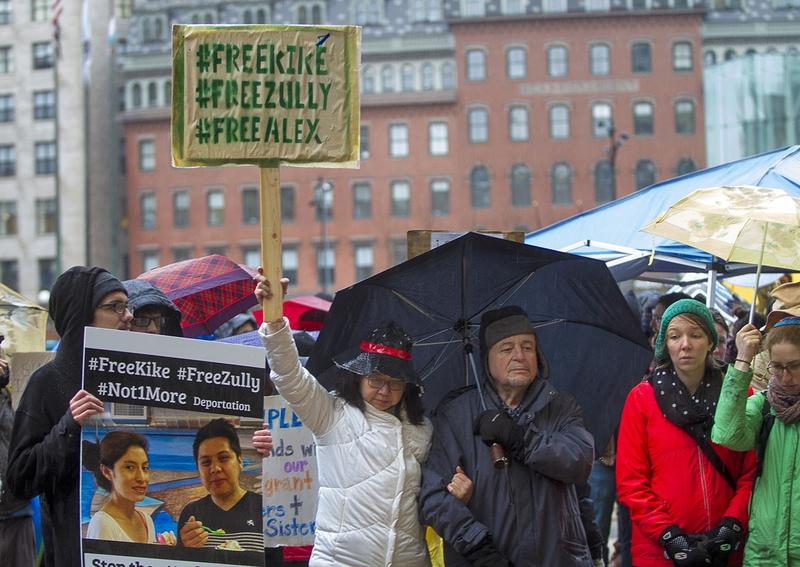 Protesters hold signs supporting the three activists outside the court house in Boston Monday.