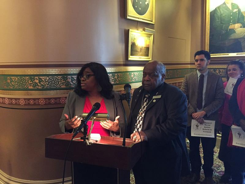 Rep. Kiah Morris, left, speaks at a podium during a Statehouse press conference about a racial justice bill back in March.