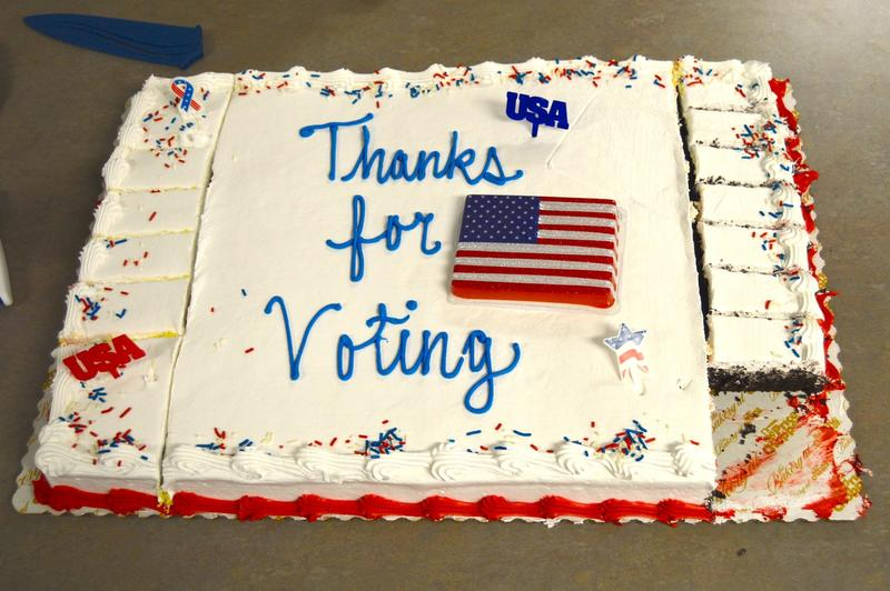 A cake with white frosting and Thanks for voting written in blue frosting with an American flag.