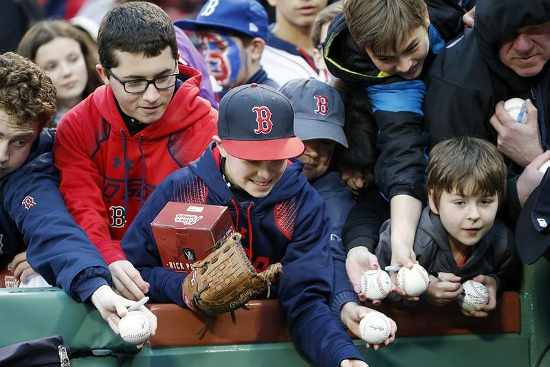 A group of fans, some wearing Boston Red Sox apparel, hold out baseballs to be autographed.