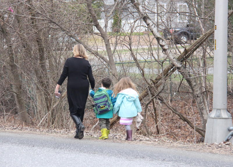 A staffer and two children who were inside a child care facility on the Essex High School campus walk away from the school after being released Wednesday.