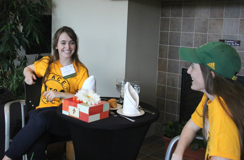 Sierra Maust, left, and Alyssa McCabe demonstrate their group's invention designed to get people interacting face-to-face.