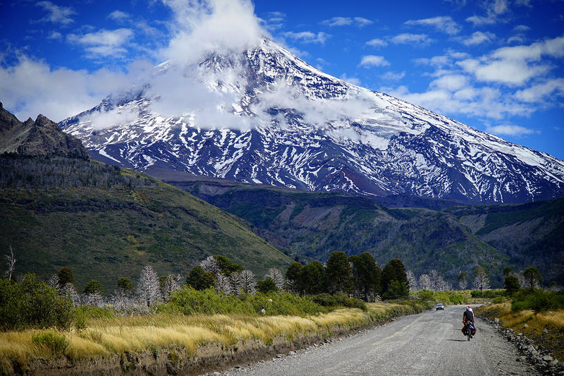 Volcan Lanin in the background as a bicycle and car travel the road below.