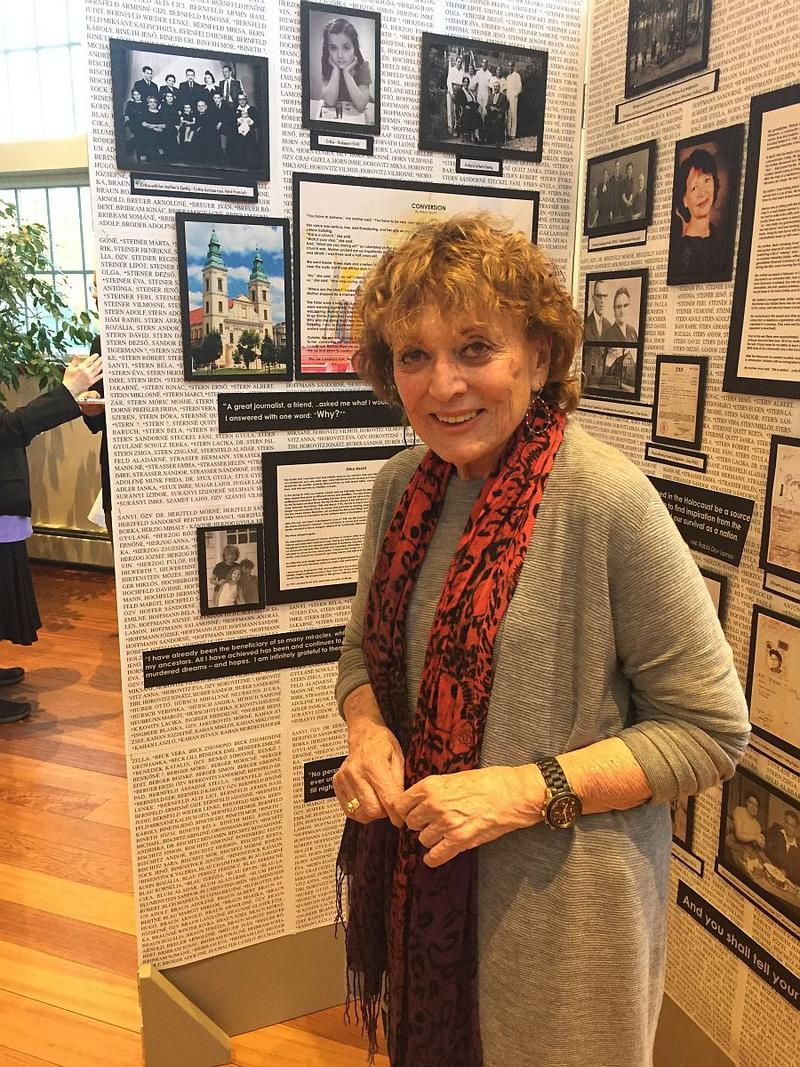 Erica Hecht is pictured at an exhibit at the Jewish Community of Greater Stowe, next to panels that tell her family's story of survival during the Holocaust.