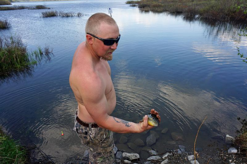 Jason Rouleau, of Williamstown, pulls a pumpkinseed sunfish out of Berlin Pond. Recreational use of the popular pond has officials struggling to balance fishing and boating access with concerns about parasites in the drinking water the pond supplies.