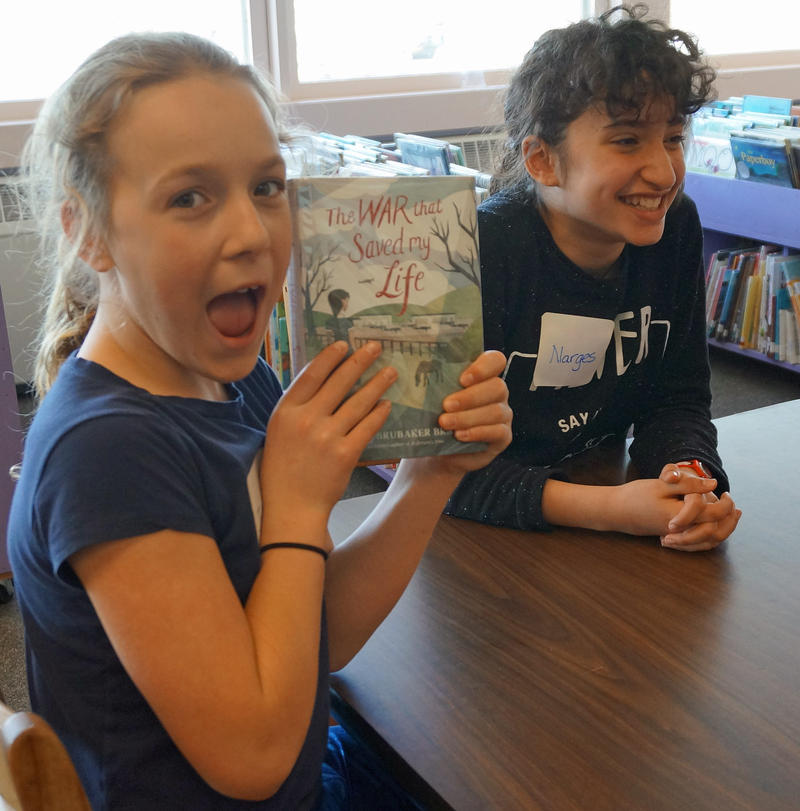 Weybridge Elementary School fourth-grader Juliette Hunsdorfer shows off a copy of 'The War That Saved My Life,' while sixth-grader Narges Anzali listens to another reader's comments about the book.