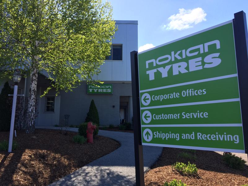 Nokian Tyres sign outside its Colchester headquarters with arrows pointing to corporate offices, customer service, and shipping and receiving.